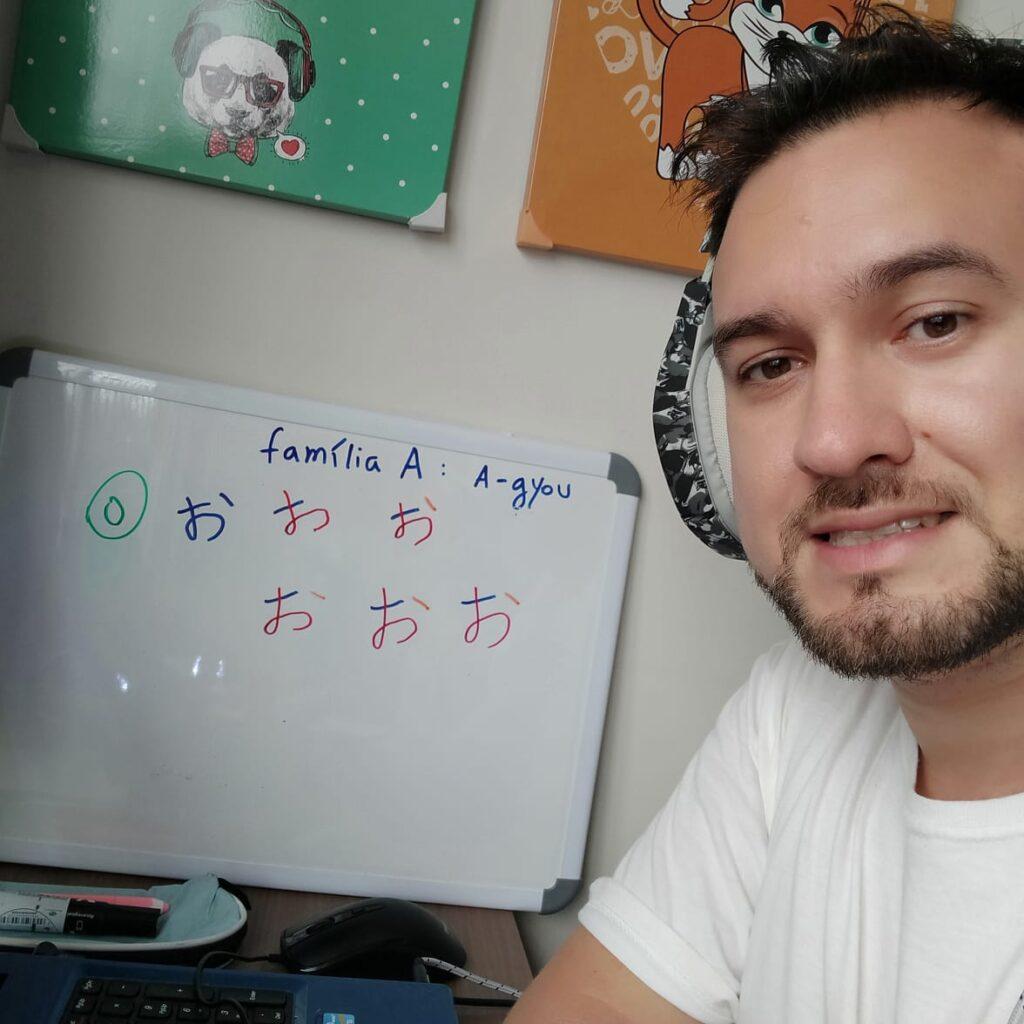 Uma selfie minha dando aula em frente ao computador, com um quadro branco ao fundo.
